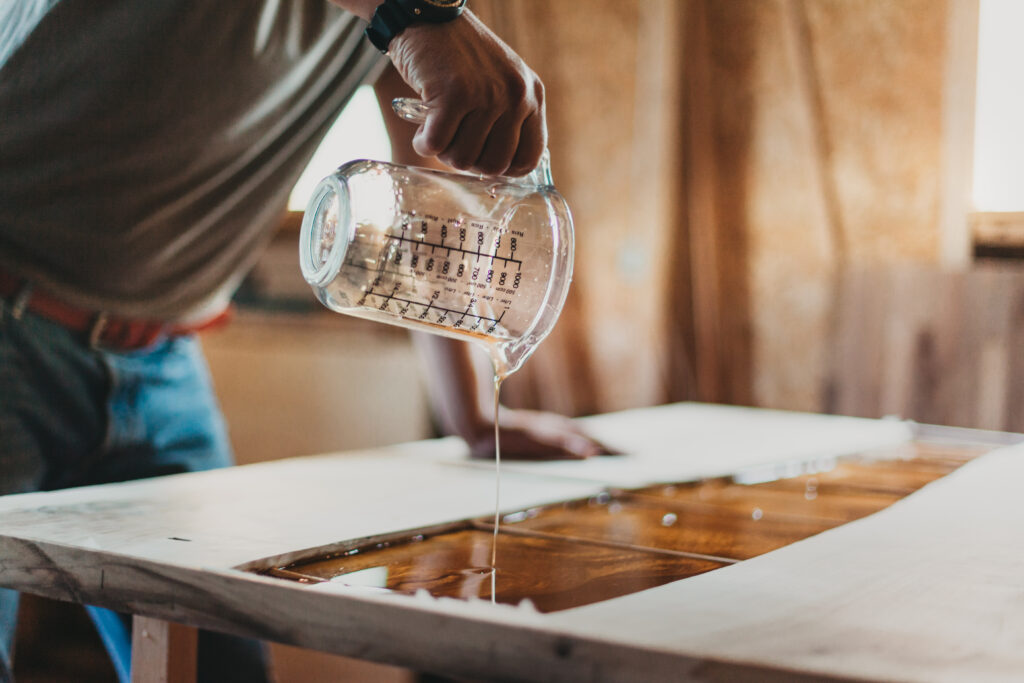 Detail of Skilled Artisan Carpenter Working on a Piece of Furniture with Epoxy Resin in his Workshop